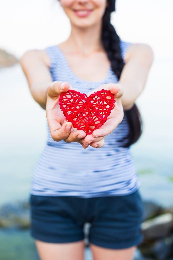 Młody caucasian uśmiechnięty brunetki kobiety mienia czerwieni serce zdjęcia stock