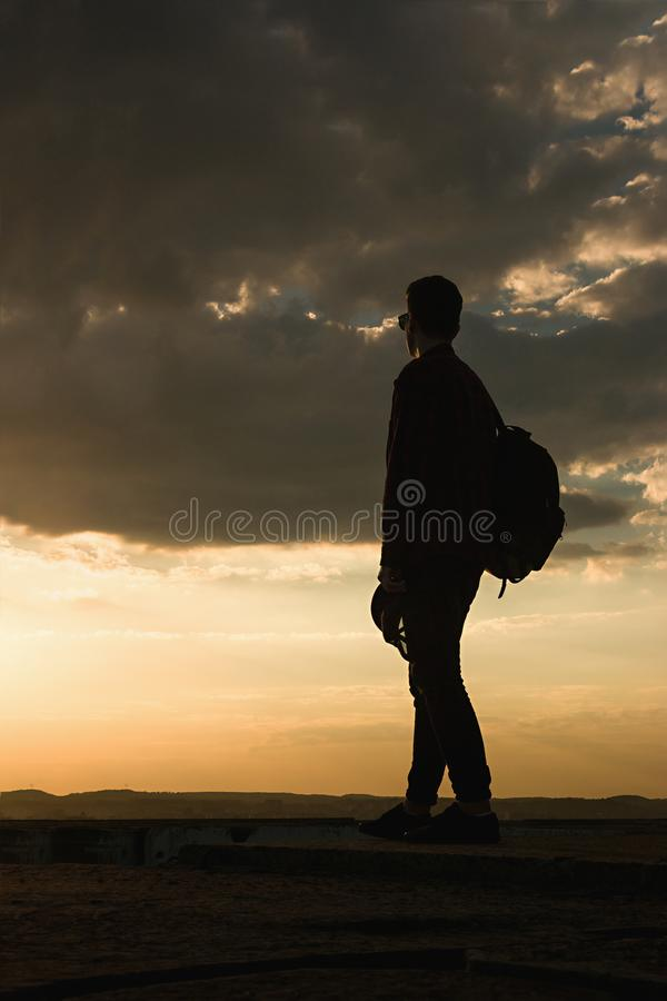 Młody chłodno facet w koszulowym plecaku i okularach przeciwsłonecznych na dachu podczas zmierzchu nieba obraz stock