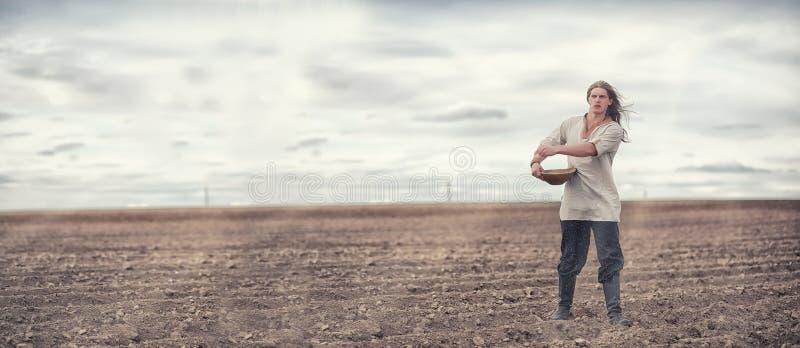 Młody chłop sia pole z adrą fotografia stock