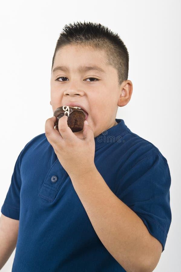 Młody chłopiec łasowania ciastko zdjęcia royalty free