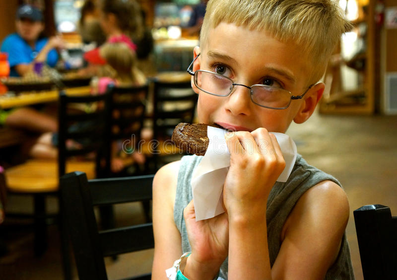 Młody chłopiec łasowania ciastko fotografia royalty free