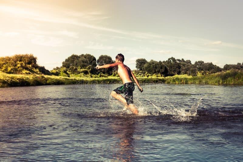 Młody chłopiec bieg naprzód na rzecznym brzeg podczas zmierzchu zdjęcie stock