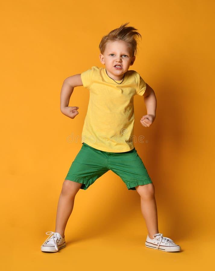 Młody chłopiec dzieciak w żółtej koszulce i zielonych skrótach demonstruje władzę i syczy z furią pozy postępują jak gniewny giga zdjęcie stock