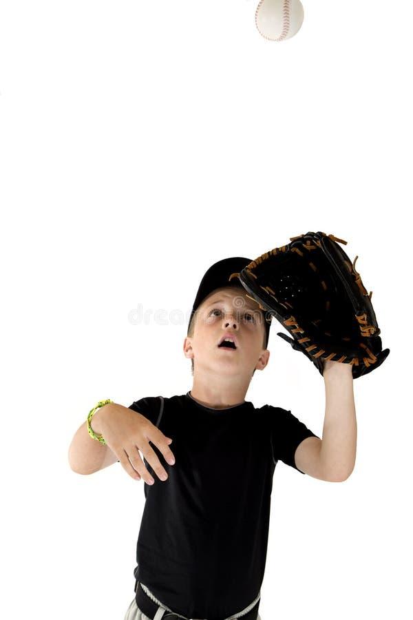 Młody chłopiec gracz baseballa skupiał się na łapać baseballa fotografia royalty free