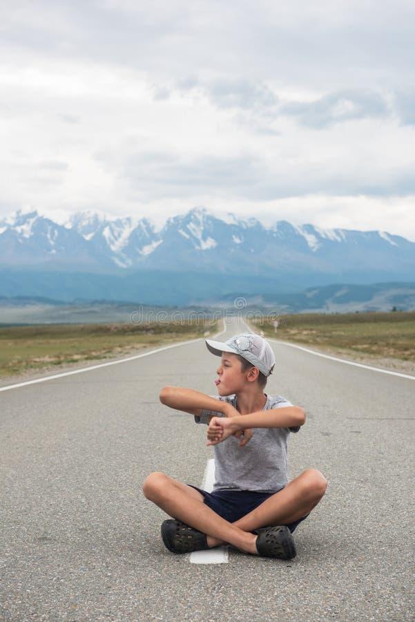 Młody chłopiec obsiadanie na drodze fotografia royalty free