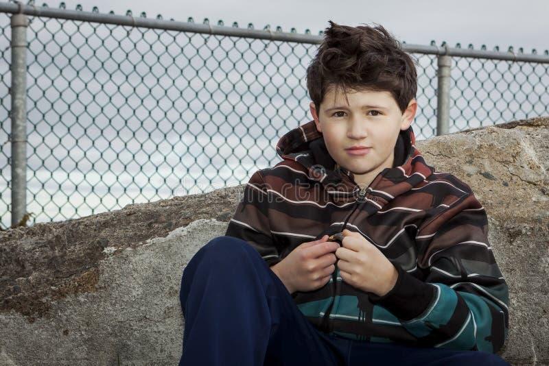 Młody chłopiec obsiadanie na skale przed Łańcuszkowego połączenia ogrodzeniem Pod Chmurnym Popielatym niebem zdjęcia stock