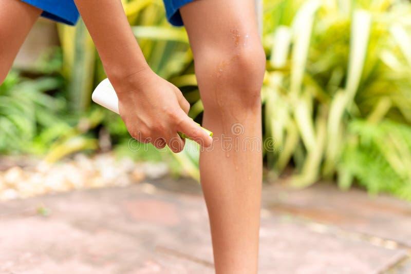 Młody chłopiec opryskiwania insekta repellent przeciw komarów kąskom na jego nogach w ogródzie fotografia royalty free