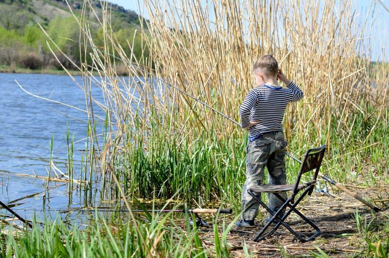Młody chłopiec połów na jeziornym brzeg fotografia stock