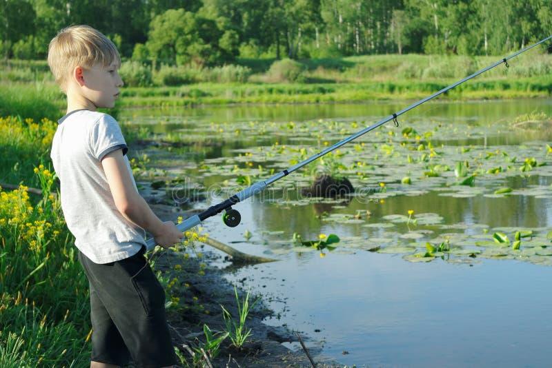 Młody chłopiec połów przy rzeki wybrzeżem zdjęcia royalty free
