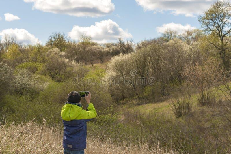 Młody chłopiec robi zdjęcia na telefonach komórkowych pięknego krajobrazu z kwitnącymi drzewami wczesną wiosną fotografia royalty free