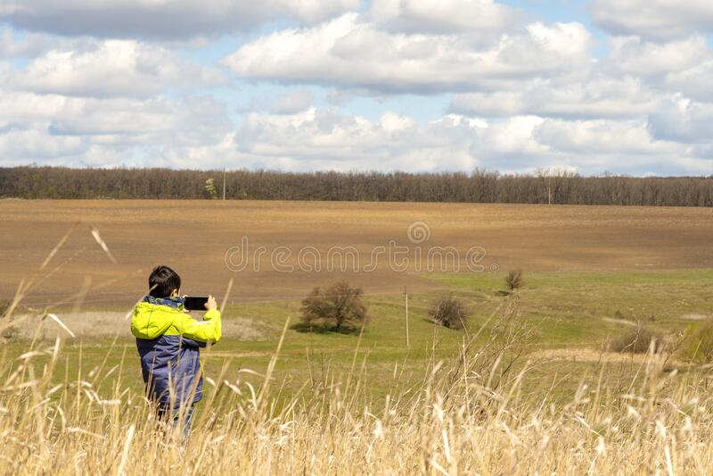Młody chłopiec robi zdjęcia na telefonach komórkowych pięknego krajobrazu z kwitnącymi drzewami wczesną wiosną zdjęcie stock