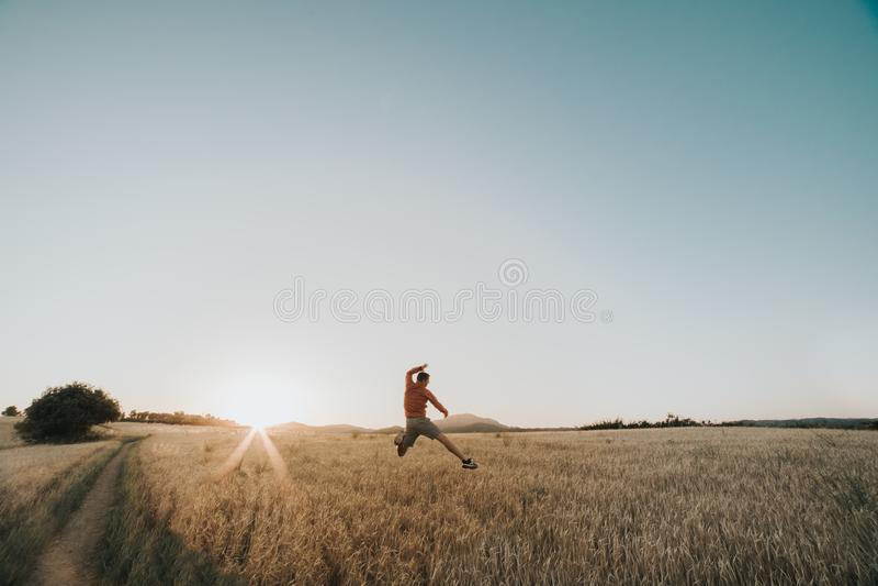 """MÅ'ody chÅ'opiec skaczÄ…cy na polu pszenicy o zachodzie sÅ'oÅ""""ca obok promieni sÅ'onecznych i x27 zdjęcie stock"""
