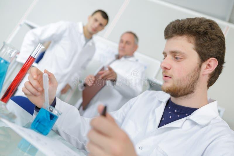 Młody chemik pracuje z tubkami w laboratorium fotografia stock