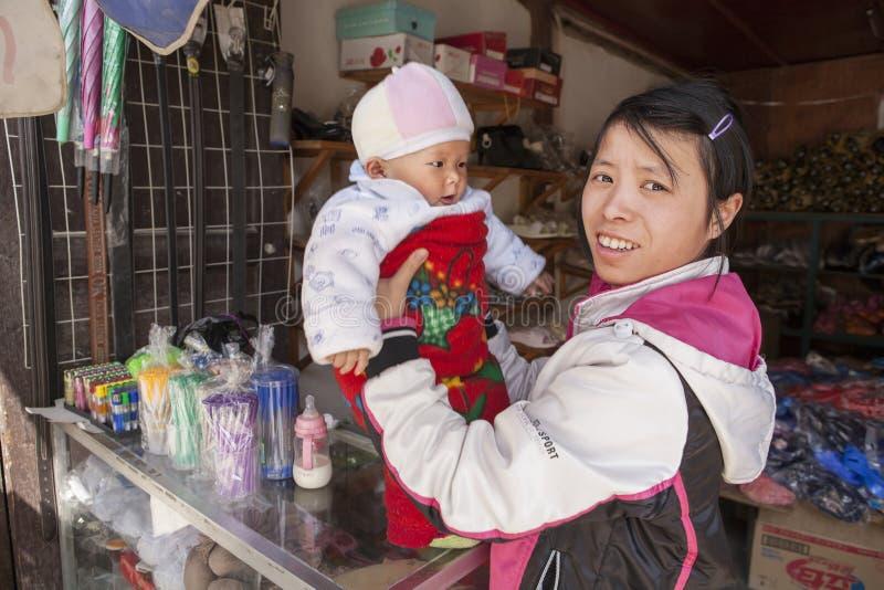 Młody Chiński dziewczyny tradeswoman trzyma dziecka na rękach zdjęcie royalty free