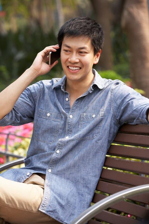 Młody Chiński Mężczyzna TARGET1167_0_ Na Parkowej Ławce obrazy stock