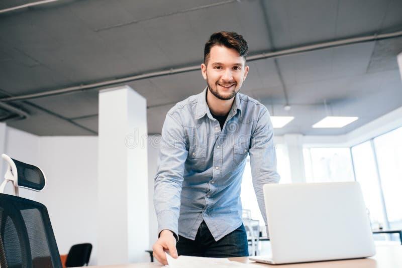 Młody ciemnowłosy mężczyzna pracuje z laptopem w biurze Jest ubranym błękitną koszula Jest uśmiechnięty kamera obrazy royalty free