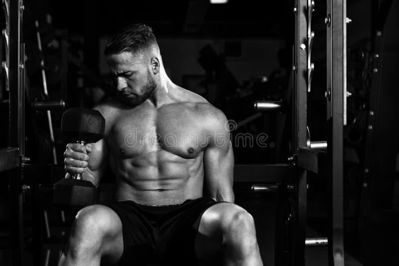 Młody Człowiek Ćwiczy bicepsy Z Dumbbells fotografia stock