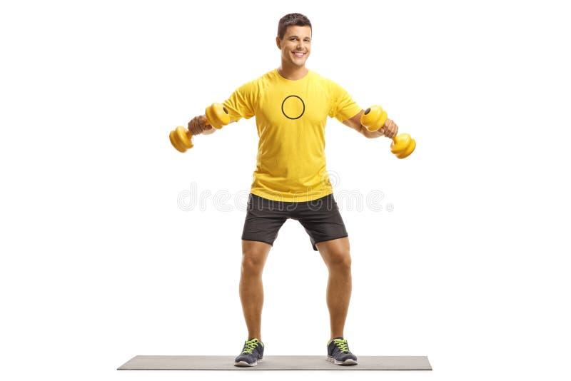 Młody człowiek ćwiczy na macie z weigths obraz stock