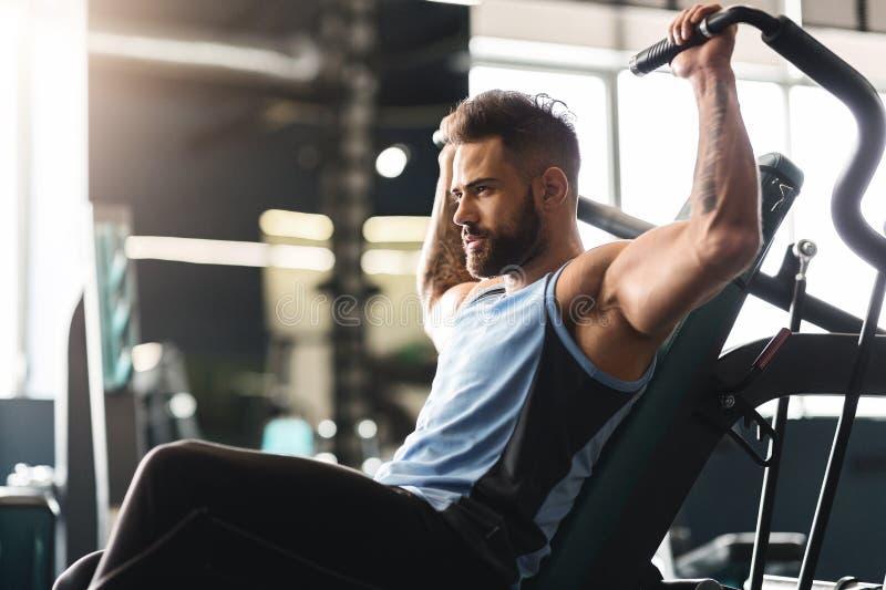 Młody człowiek ćwiczy z stażowym aparatem w gym, opróżnia przestrzeń zdjęcia royalty free