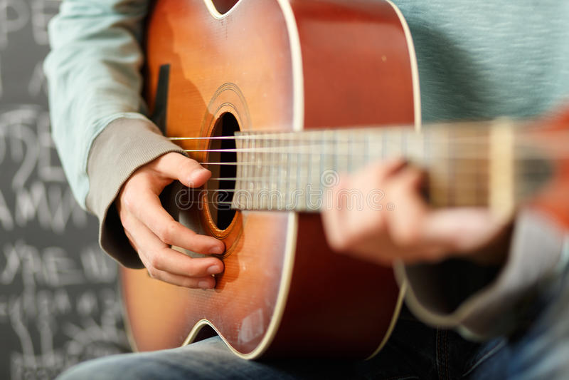 Młody człowiek bawić się gitarę akustyczną zdjęcie royalty free