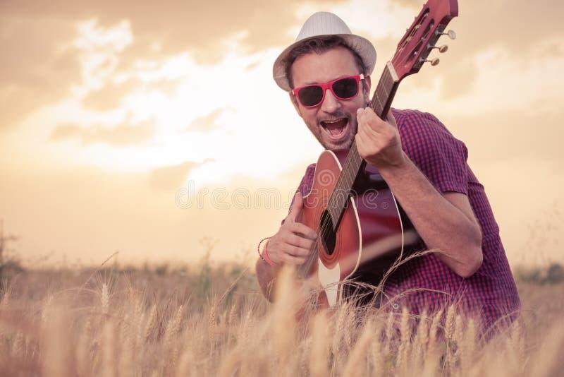 Młody człowiek bawić się gitarę akustyczną i śpiew outdoors obrazy royalty free