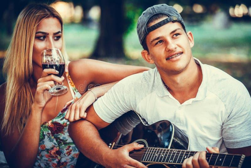 Młody człowiek bawić się gitarę dla jego dziewczyny zdjęcie stock