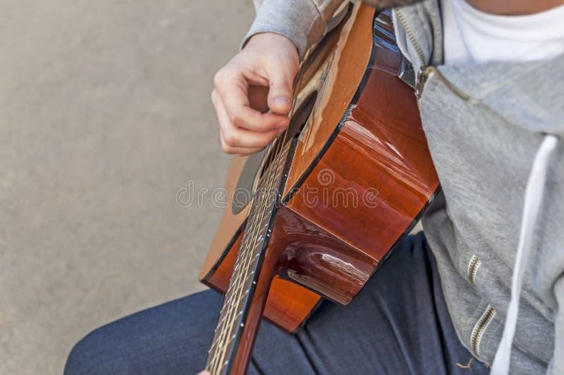 Młody człowiek bawić się gitarę na ławce w jesień parku, spojrzenie od above obraz royalty free