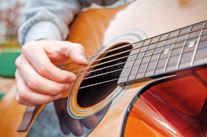 Młody człowiek bawić się gitary akustycznej zamkniętego up outdoors w jesień parku zdjęcia stock