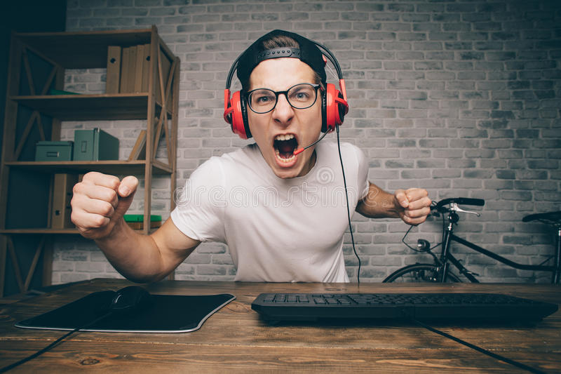Młody człowiek bawić się grę w domu i leje się wideo playthrough lub walkthrough zdjęcia royalty free