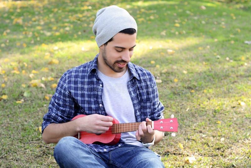 Młody człowiek bawić się ukelele w parku obrazy stock