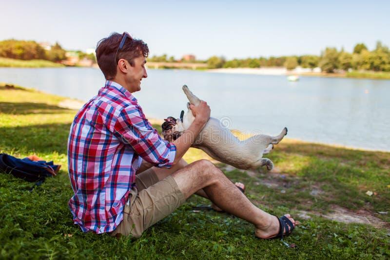 Młody człowiek bawić się z mopsa psa obsiadaniem na trawie Szczęśliwy szczeniak ma zabawę z mistrzem zdjęcia stock