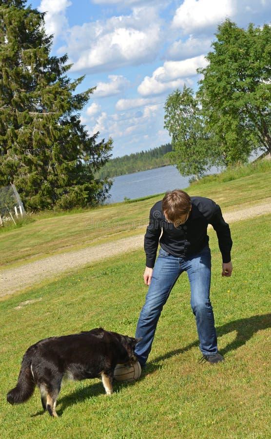 Młody człowiek bawić się z psem w futbolu w Fińskim Lapland niebezpieczny moment zdjęcia stock