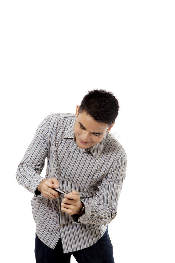 Młody człowiek bawić się z smartphone na studiu obrazy stock
