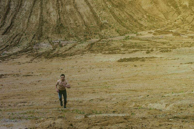 Młody człowiek biega w piaskowatym jarze w szarych rajstopy Pojęcie zdrowy styl życia fotografia royalty free