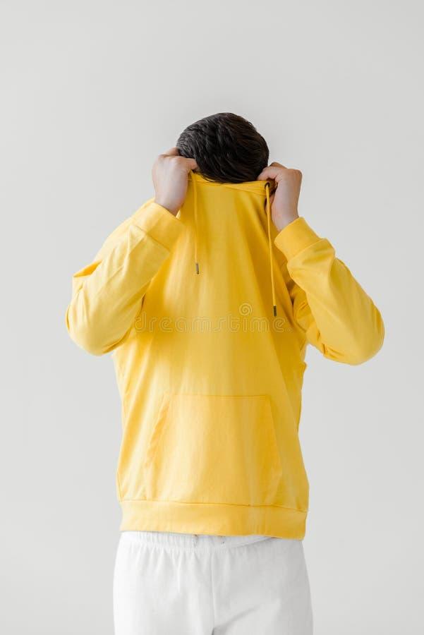 młody człowiek bierze daleko żółtego hoodie odizolowywającego na bielu obraz stock
