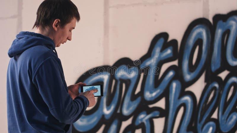Młody człowiek bierze fotografię jego ścienni graffiti na telefonie zdjęcie royalty free