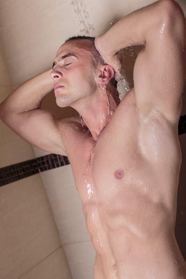 Młody człowiek bierze prysznic zdjęcie royalty free