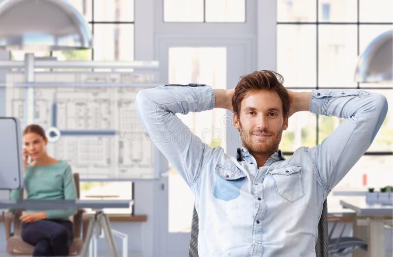 Młody człowiek bierze przerwę praca przy architekta biurem zdjęcie stock
