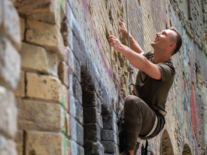 Młody człowiek bouldering plenerowego pięcie fotografia stock