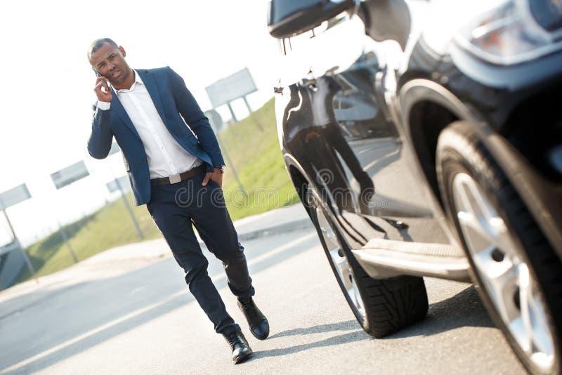 Młody człowiek chodzi samochód opowiada na smartphone poważnym obraz royalty free