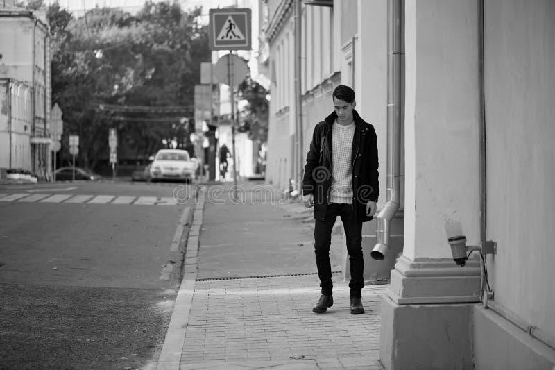 Młody człowiek chodzi w dół ulicę z ciemnym włosy i oczami lifestyle Wysoki wzrost obrazy stock