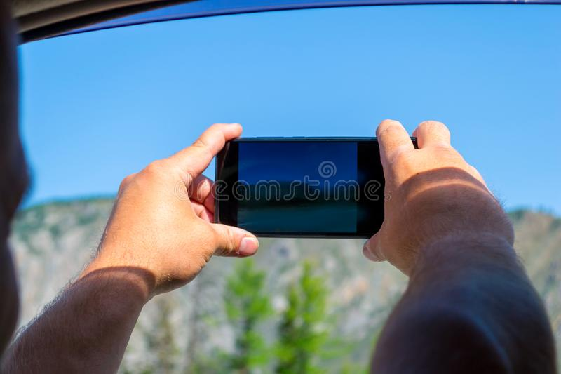 Młody człowiek ciągnie dwa kosmatej ręki w otwarte okno mo obraz stock
