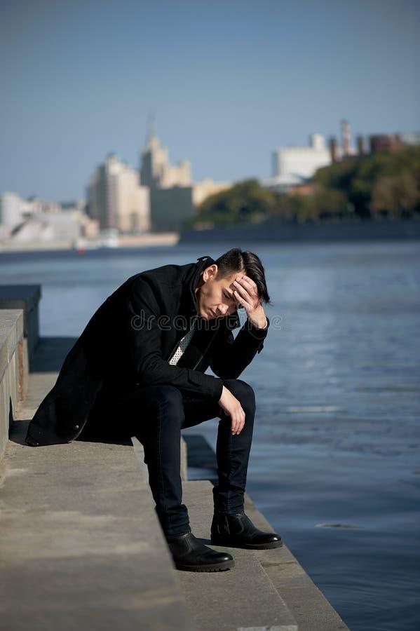Młody człowiek, cienki Z ciemnego włosy i brązu oczami Siedzieć na krokach blisko wody Smutny wielkiego miasta tła miejskiego lud obraz royalty free