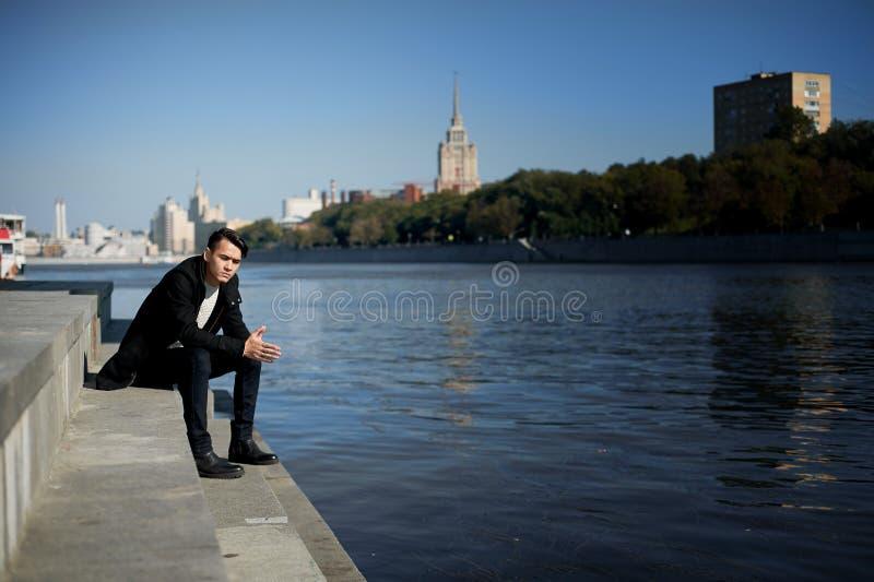 Młody człowiek, cienki Z ciemnego włosy i brązu oczami Siedzieć na krokach blisko wody Smutny wielkiego miasta tła miejskiego lud zdjęcie stock