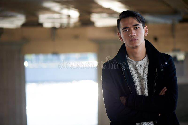 Młody człowiek, cienki Z ciemnego włosy i brązu oczami Stojący pod mostem rzeką, ręki krzyżowali nad jego klatką piersiową fotografia stock