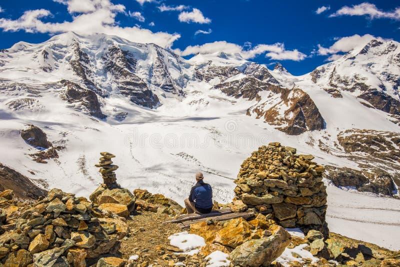 Młody człowiek cieszy się oszałamiająco widok Bernina pasmo górskie i Morteratsch lodowiec zdjęcie royalty free