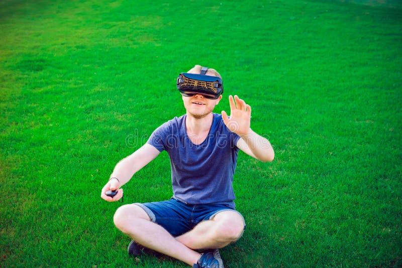 Młody człowiek cieszy się rzeczywistość wirtualna szkieł słuchawki lub 3d widowiska siedzi na zielonym gazonie w miasto parku out obraz stock