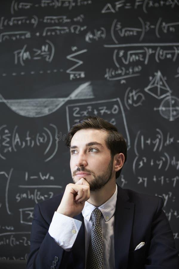 Młody człowiek contemplaiting przed blackboard zdjęcie royalty free