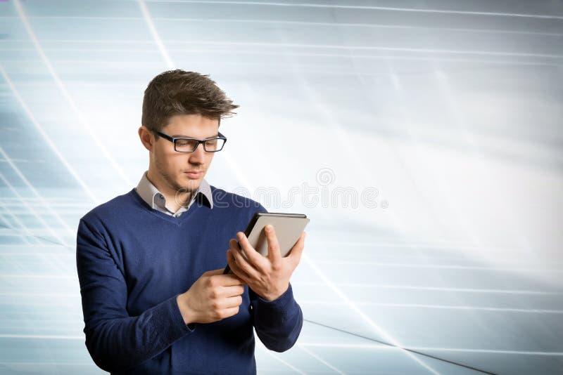 Młody człowiek czyta ebook z koszula i pulowerem zdjęcie stock