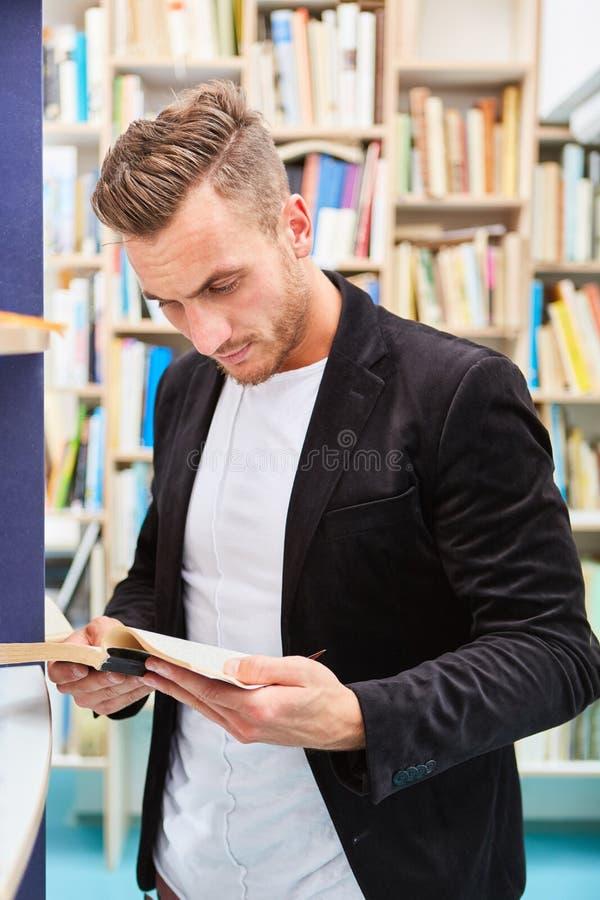 Młody człowiek czyta książkę w bibliotece obraz stock